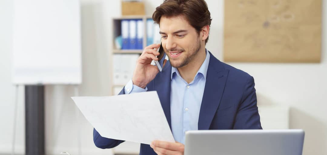 Young business man speaking in mobile phone and holding paper in his left hand infront of laptop at desk