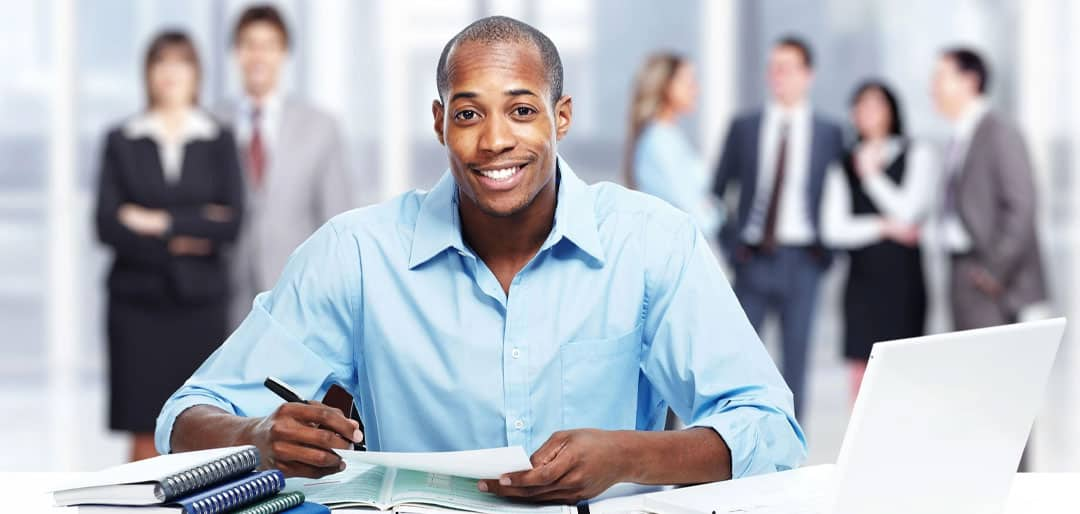 Young black man writing in an interview with group of white people behind